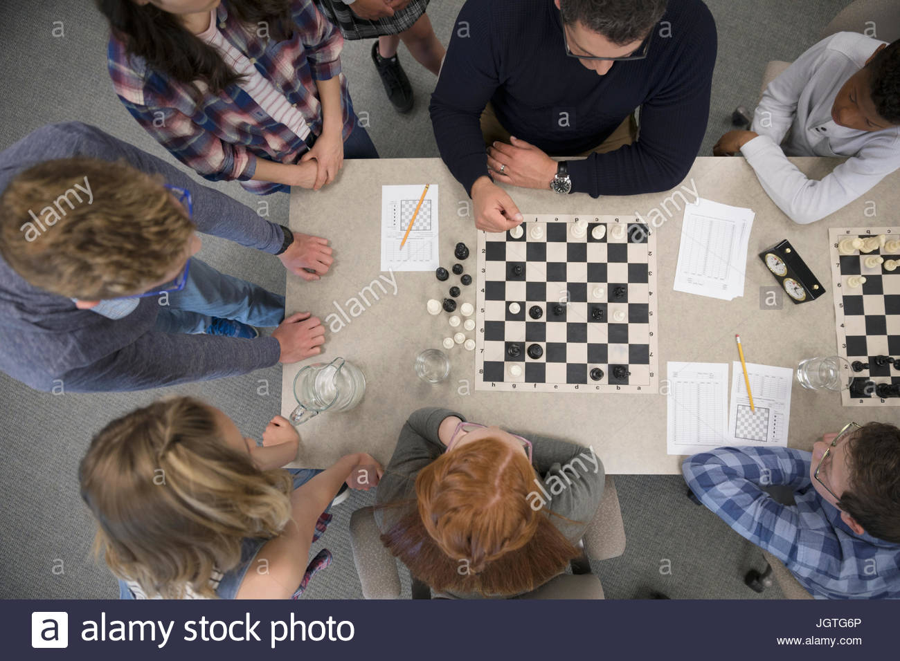 Teacher and middle school students playing chess in chess club Stock Photo