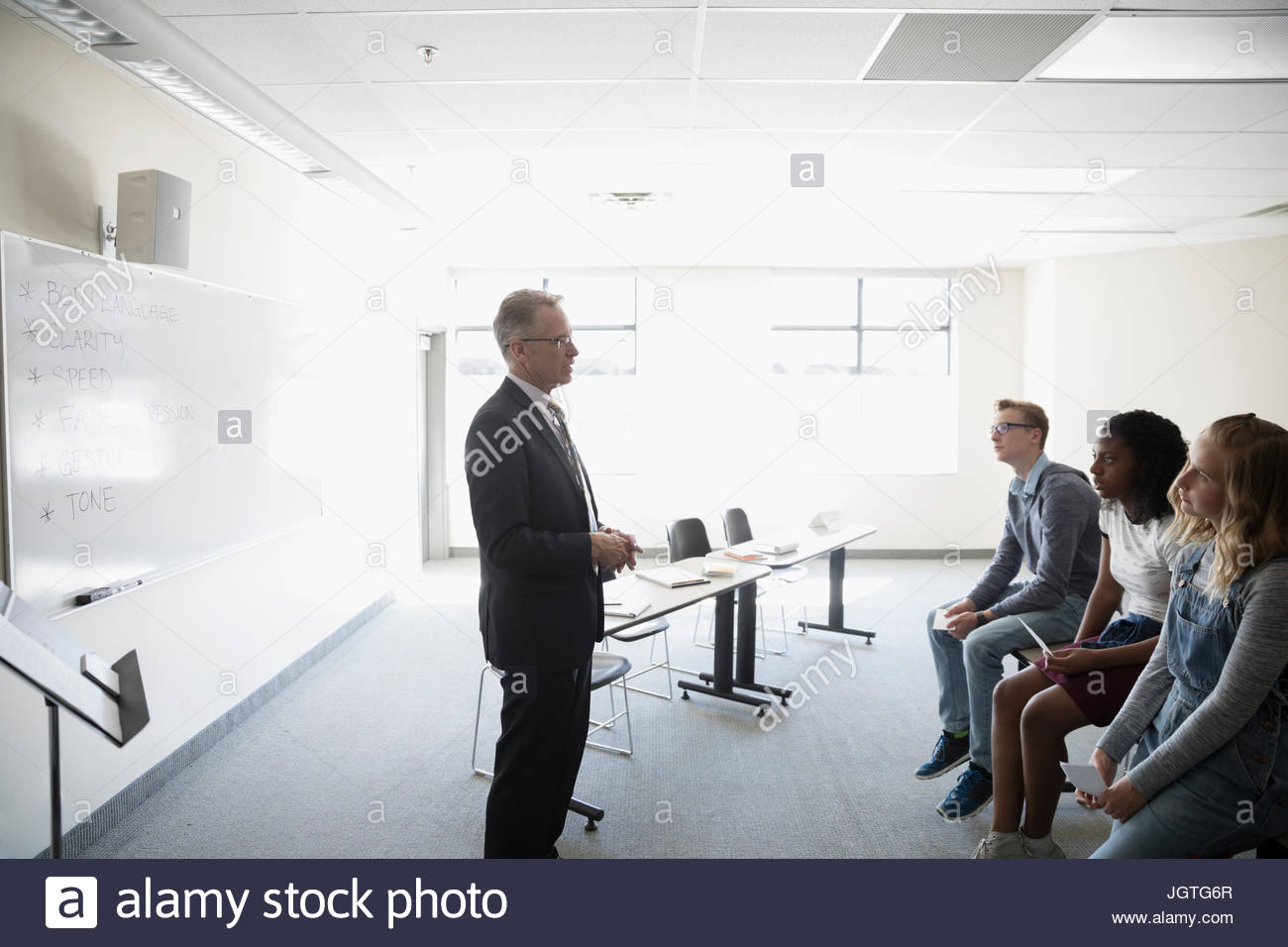 Teacher talking to middle school students in debate club classroom - Stock Image