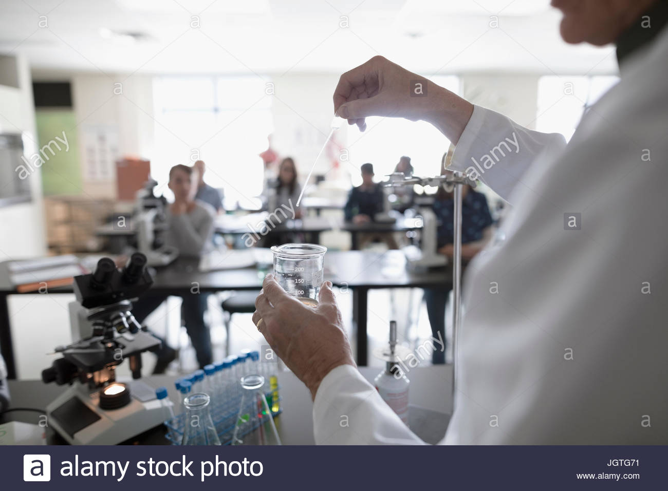Students watching science teacher conducting scientific experiment in laboratory - Stock Image