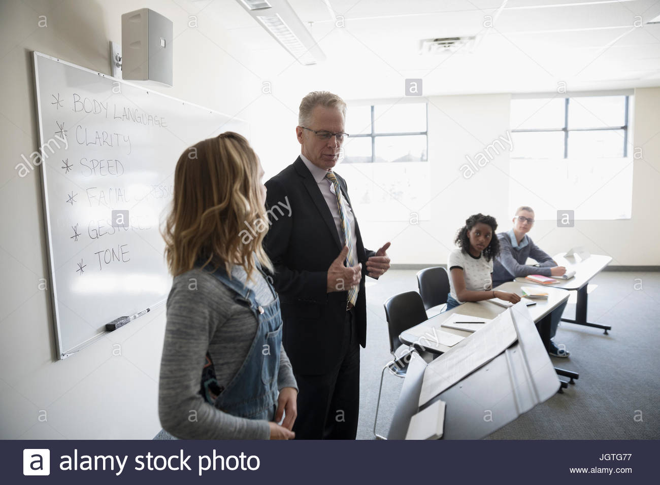 Teacher guiding girl middle school student in debate club classroom - Stock Image