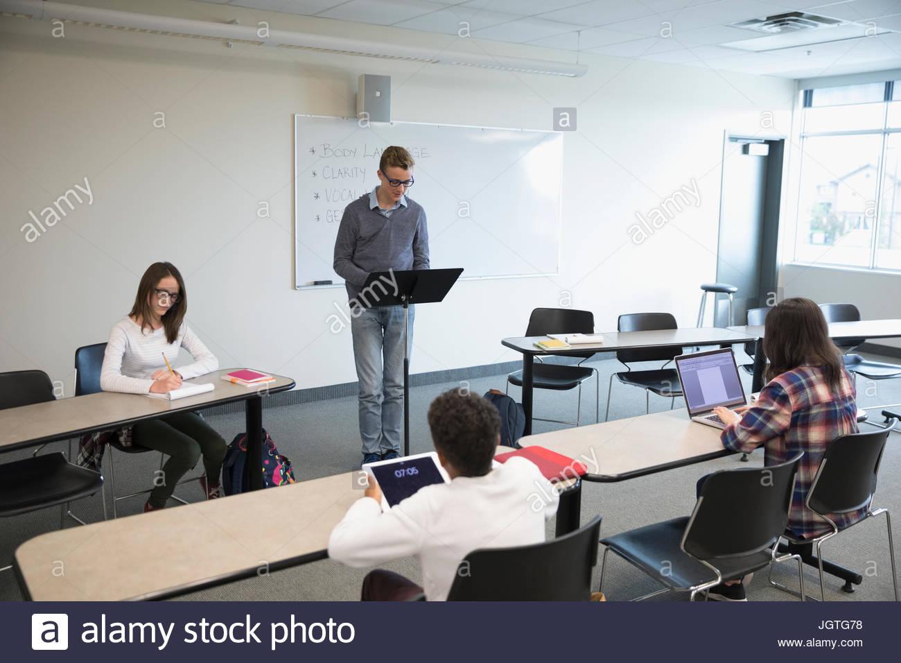 Boy middle school student speaking in debate club in classroom - Stock Image