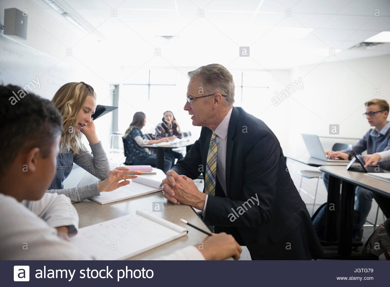Teacher and middle school students talking in classroom - Stock Image