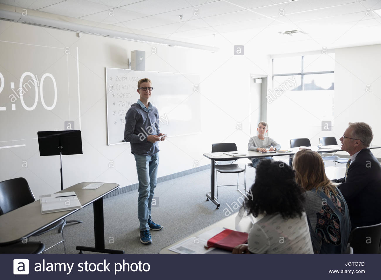 Boy middle school student speaking in debate club classroom - Stock Image