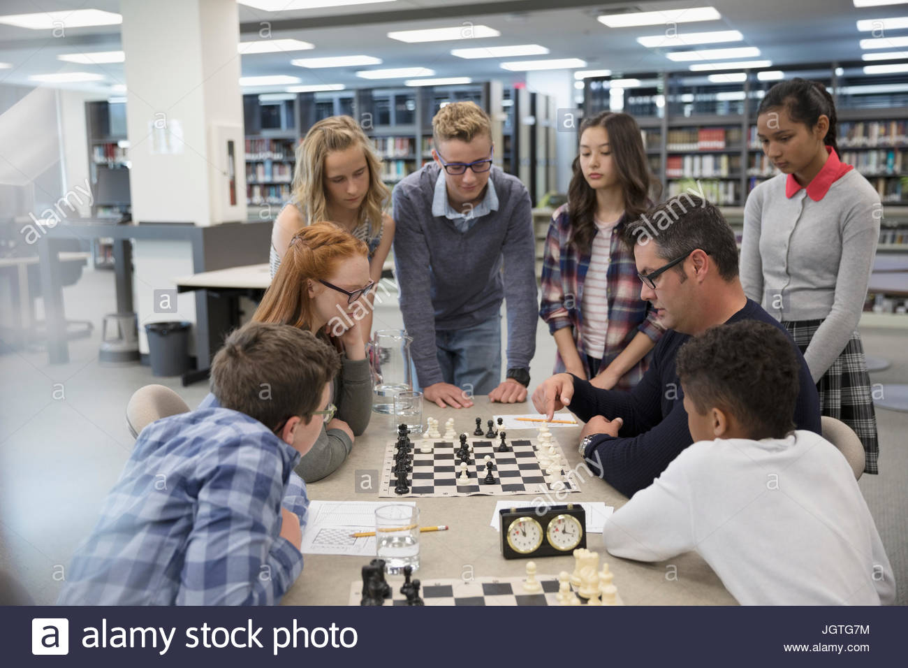 Teacher helping middle school students playing chess in chess club Stock Photo