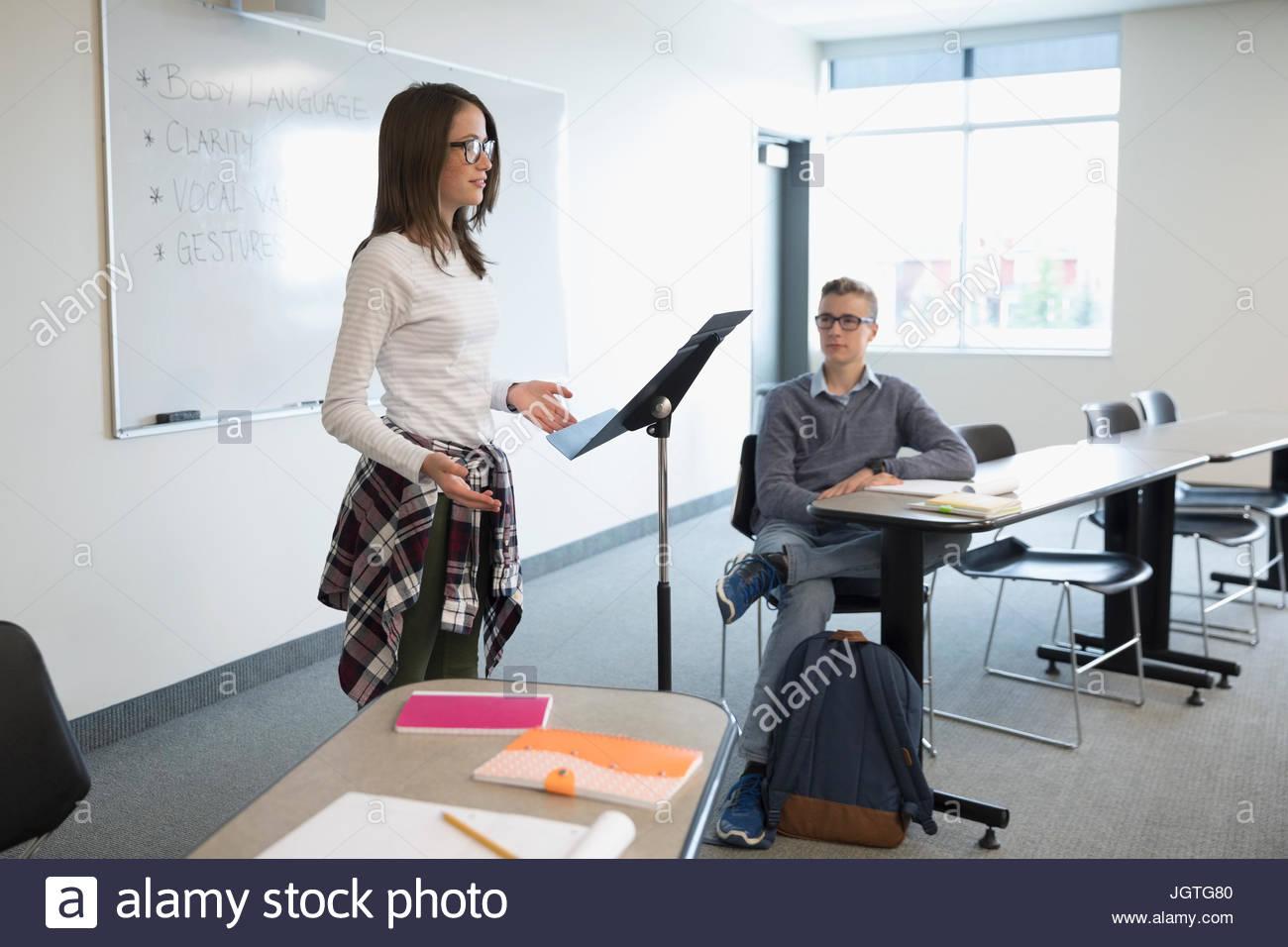 Girl middle school student speaking in debate club in classroom - Stock Image