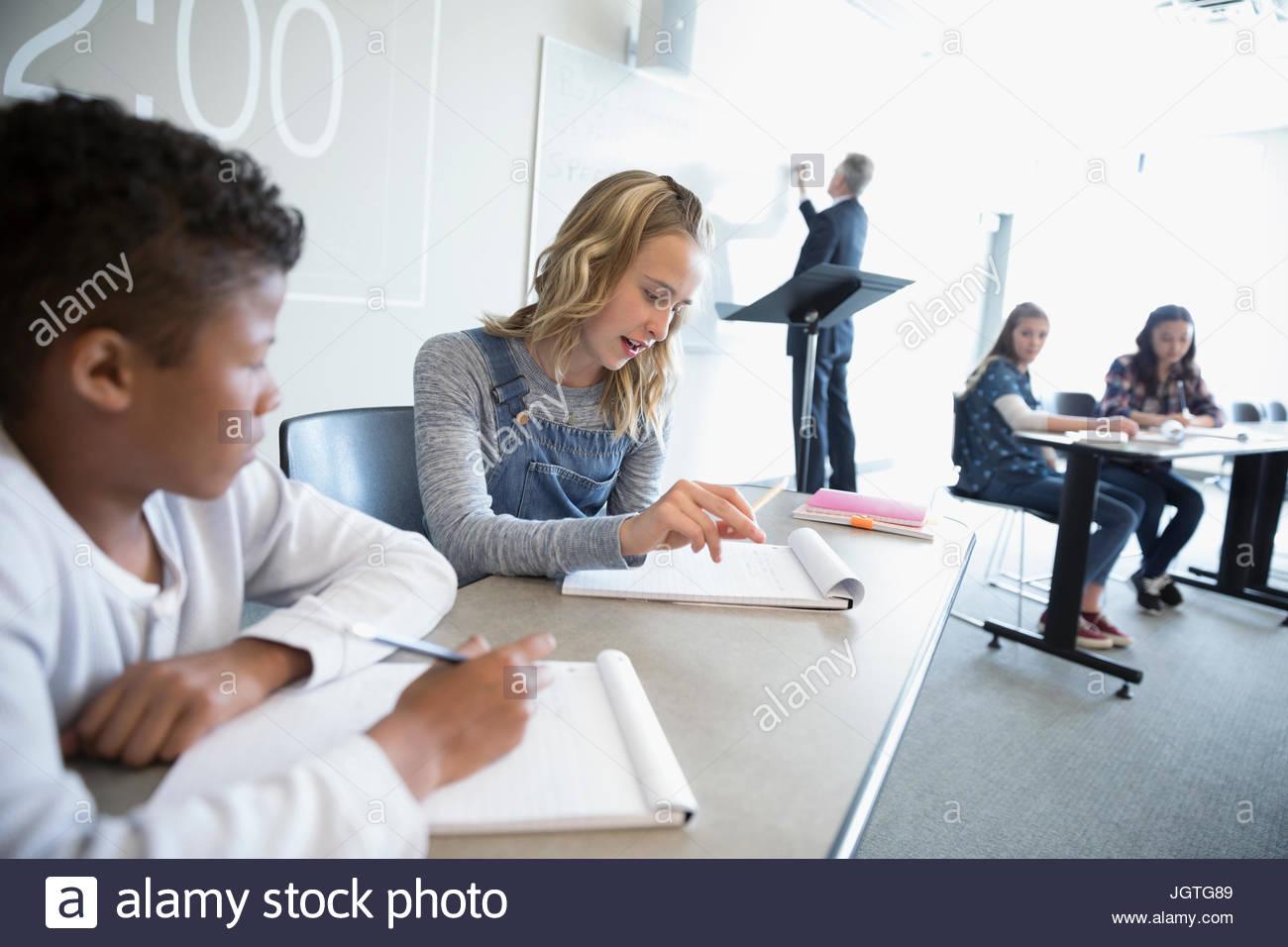 Middle school students talking in debate club in classroom - Stock Image