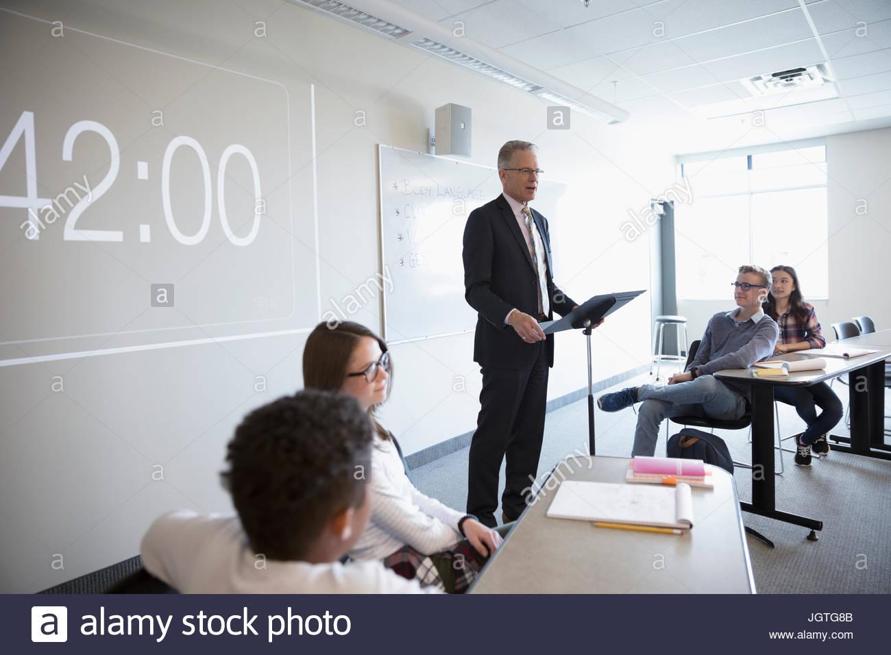 Teacher leading debate club lesson in classroom - Stock Image