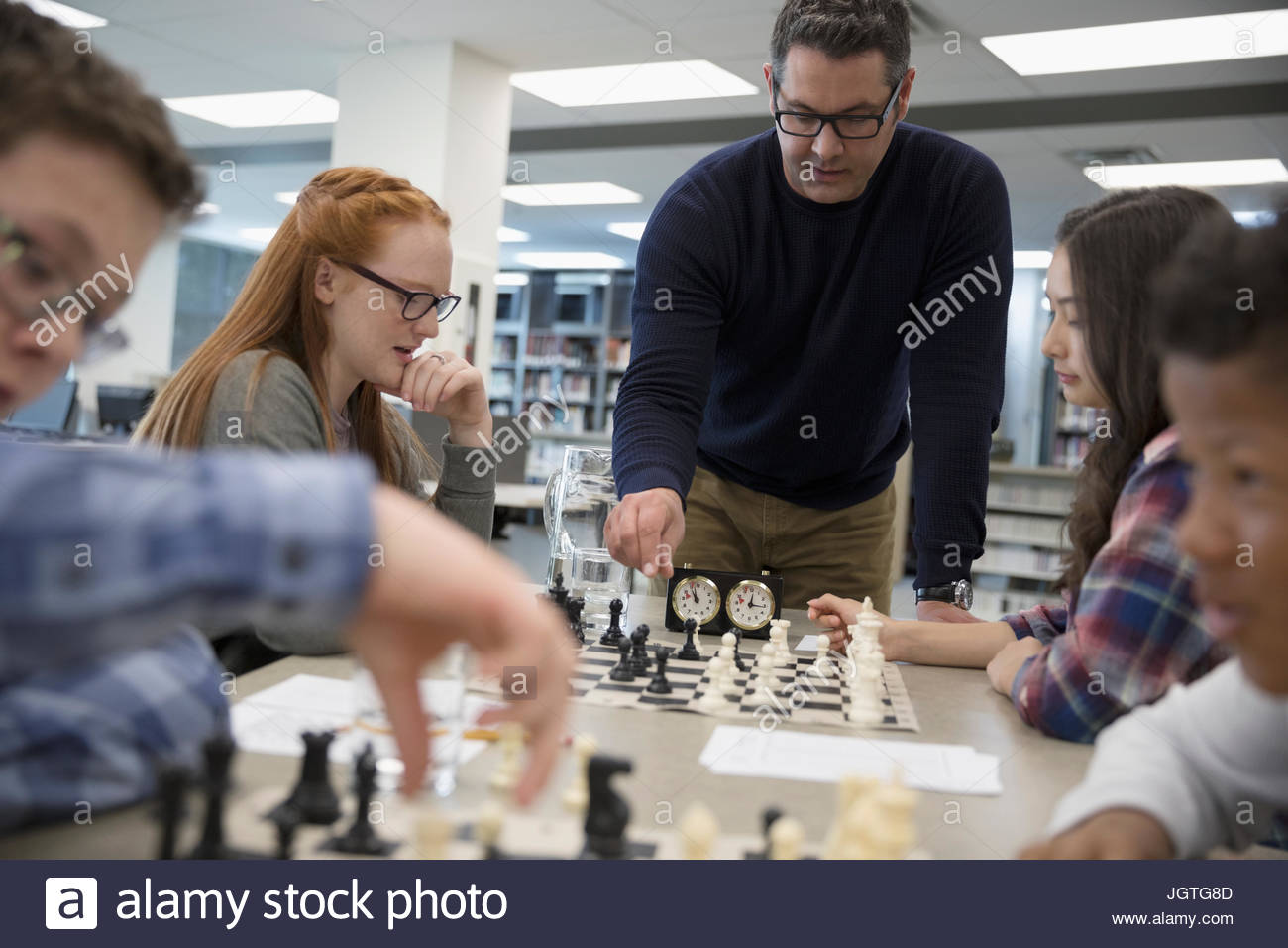 Teacher helping middle school students playing chess in chess club - Stock Image