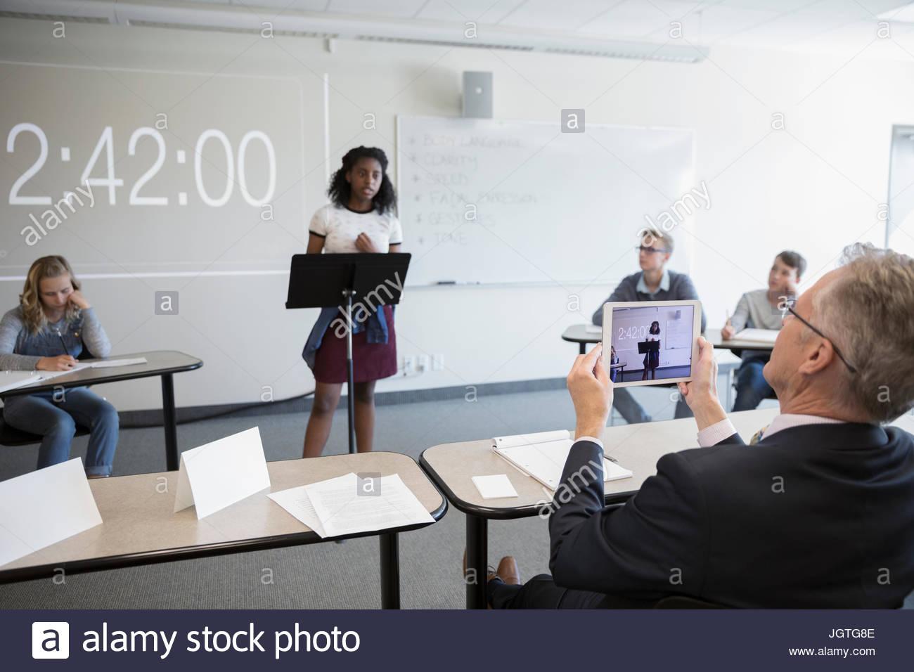 Teacher with digital tablet videoing girl middle school student speaking in debate classroom - Stock Image