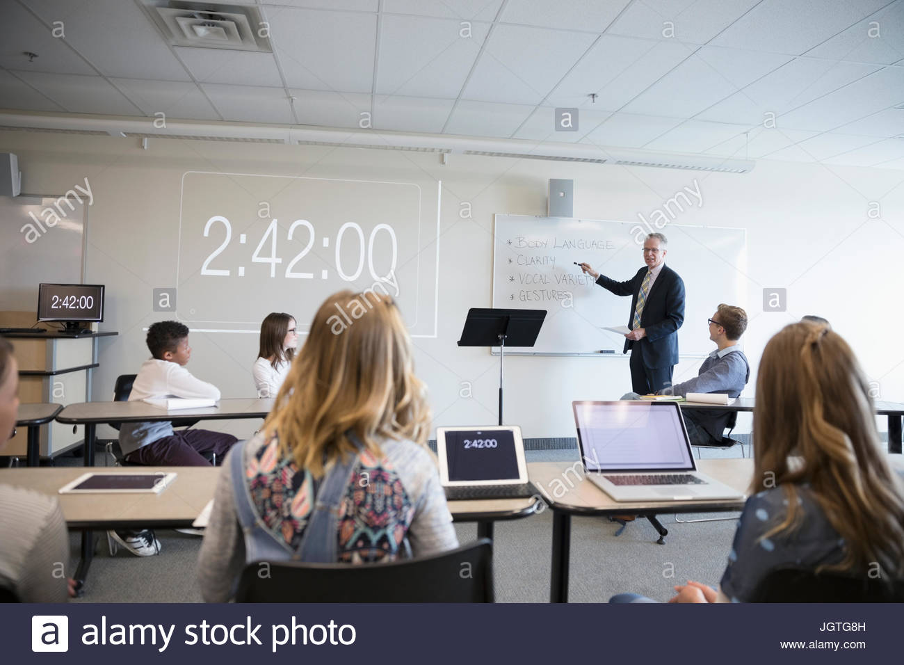 Teacher leading debate club lesson in classroom - Stock Image