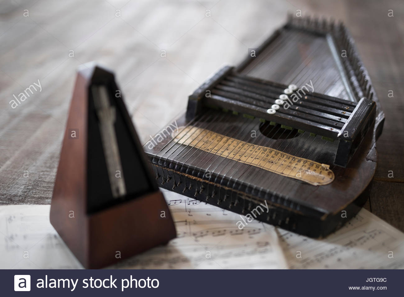 Still life vintage metronome and zither on sheet music Stock Photo