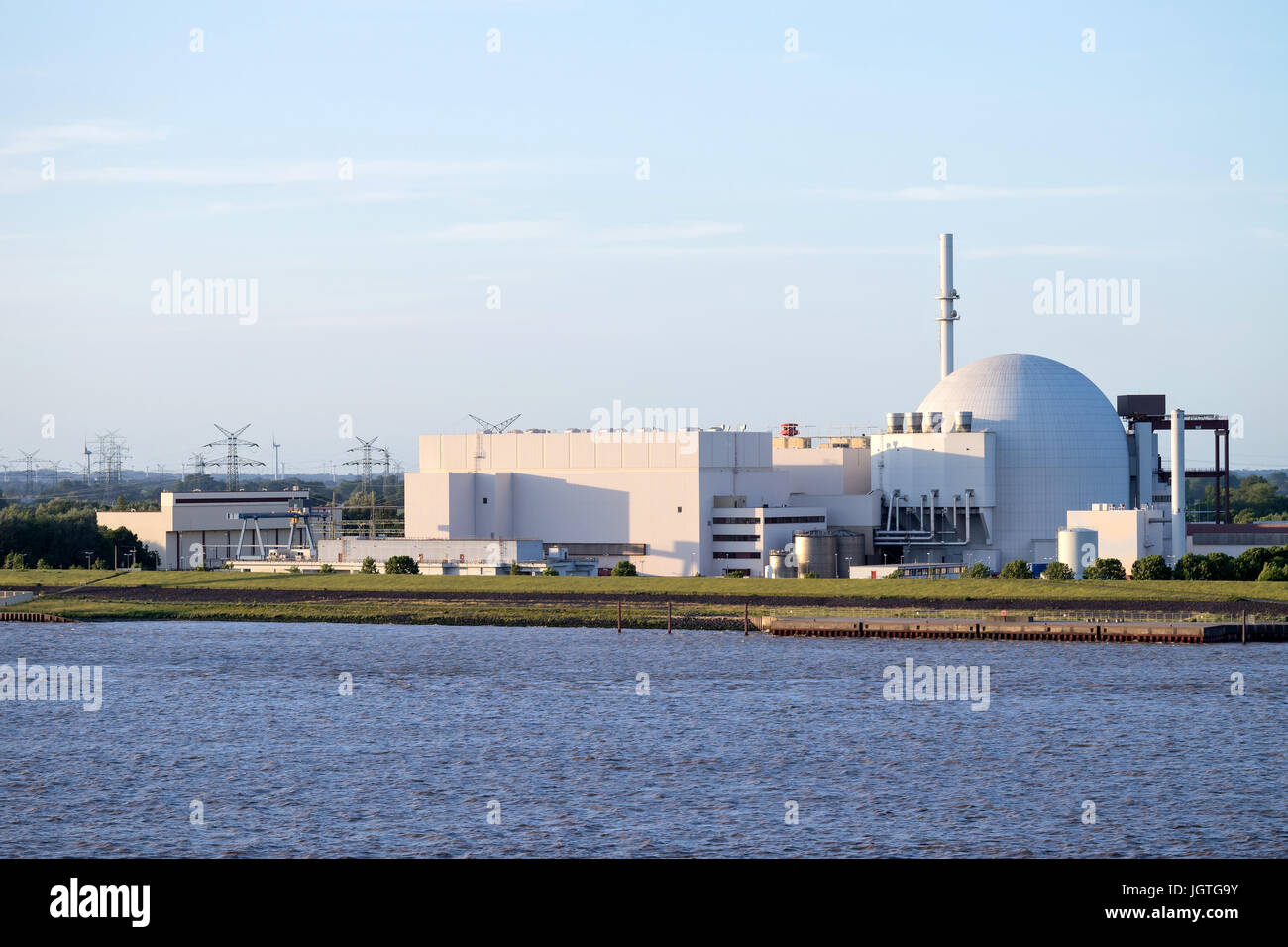 Riverside view of Brokdorf Nuclear Power Plant. It started in October 1986 and the decommissioning is planned for - Stock Image