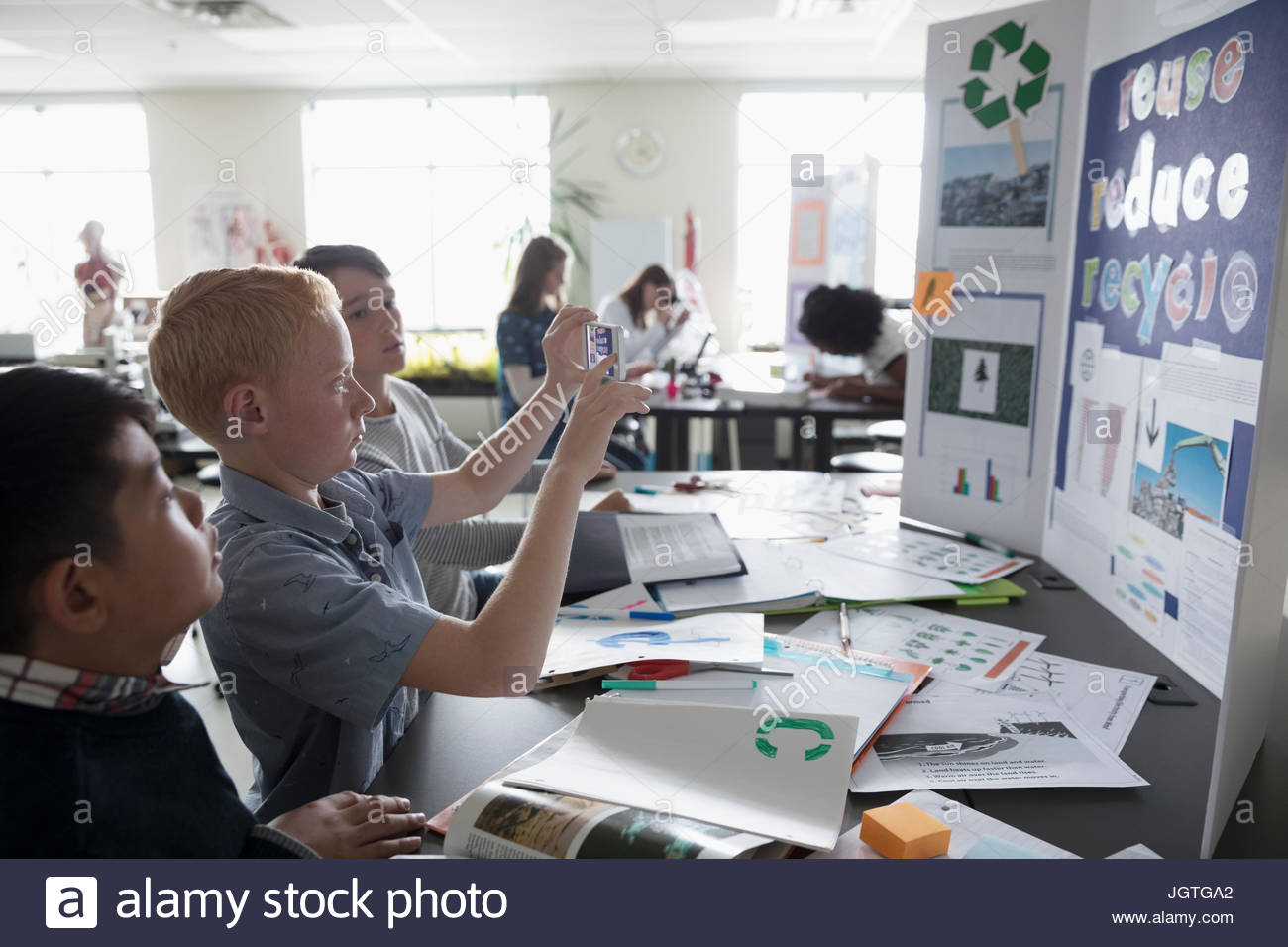 boy middle school student photographing science project poster with