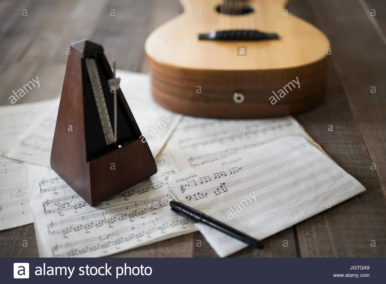 Still life of metronome, sheet music and guitar - Stock Image