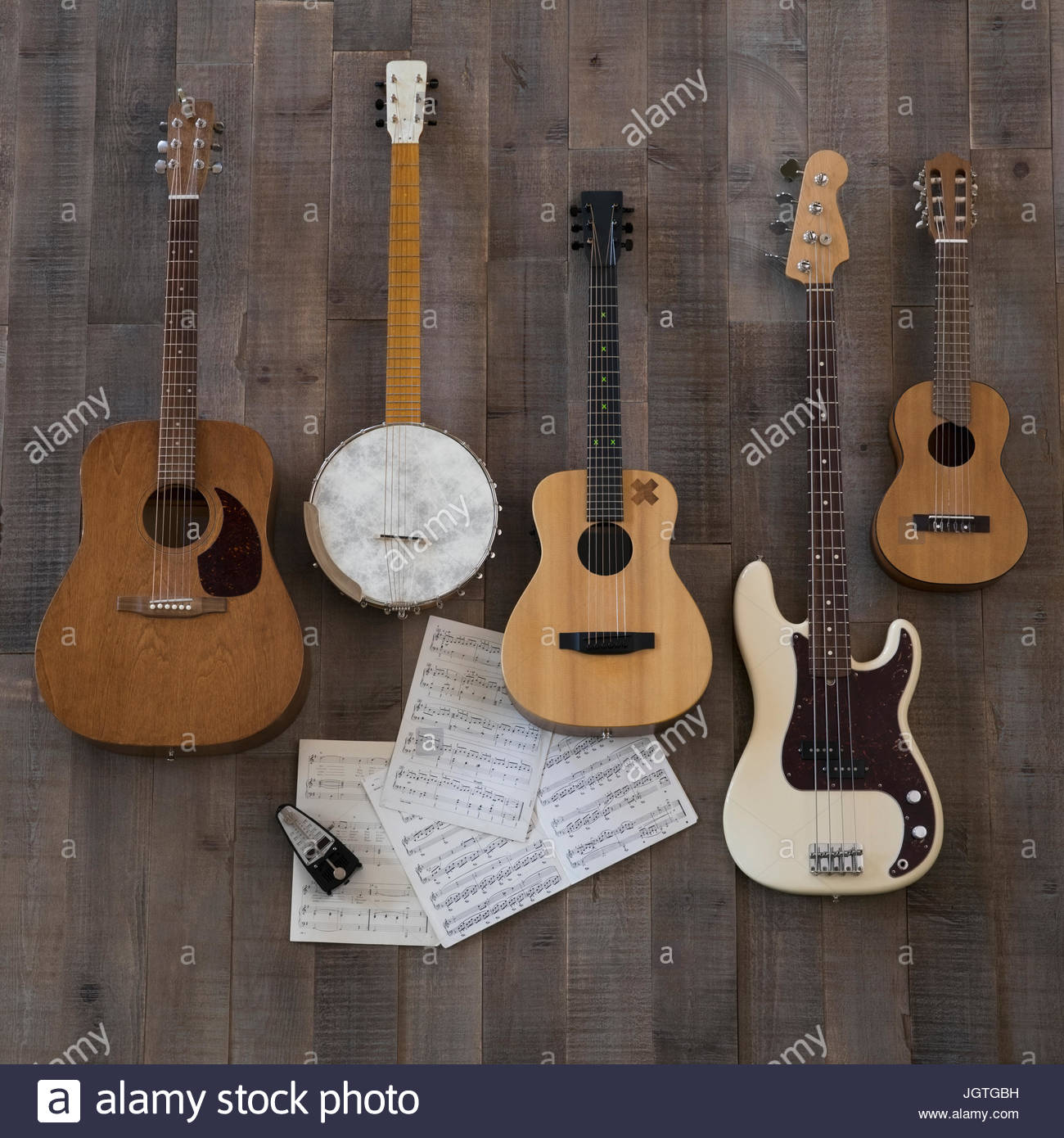 Knolling of guitars, banjo and ukulele on sheet music - Stock Image