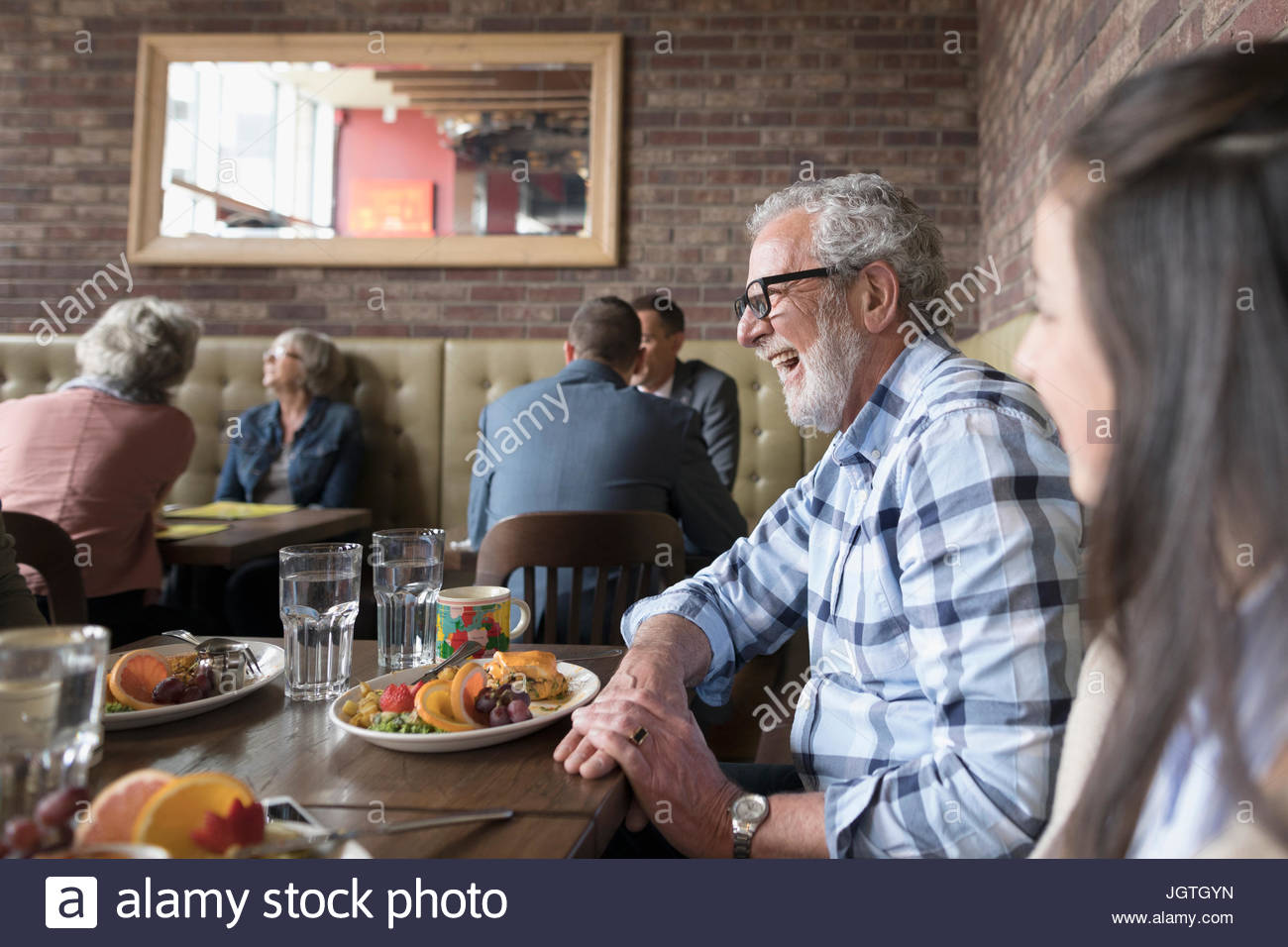 Senior man laughing and eating brunch at diner table - Stock Image