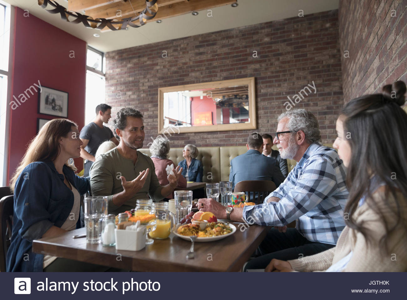 Multi-generation family talking and eating brunch at diner table - Stock Image