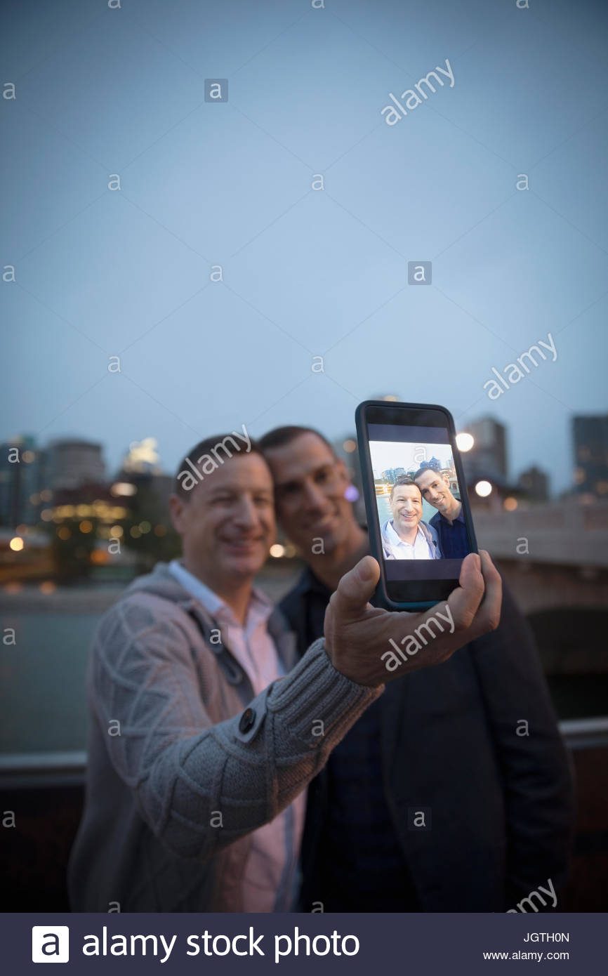 Male gay couple taking selfie with camera phone at urban river waterfront - Stock Image