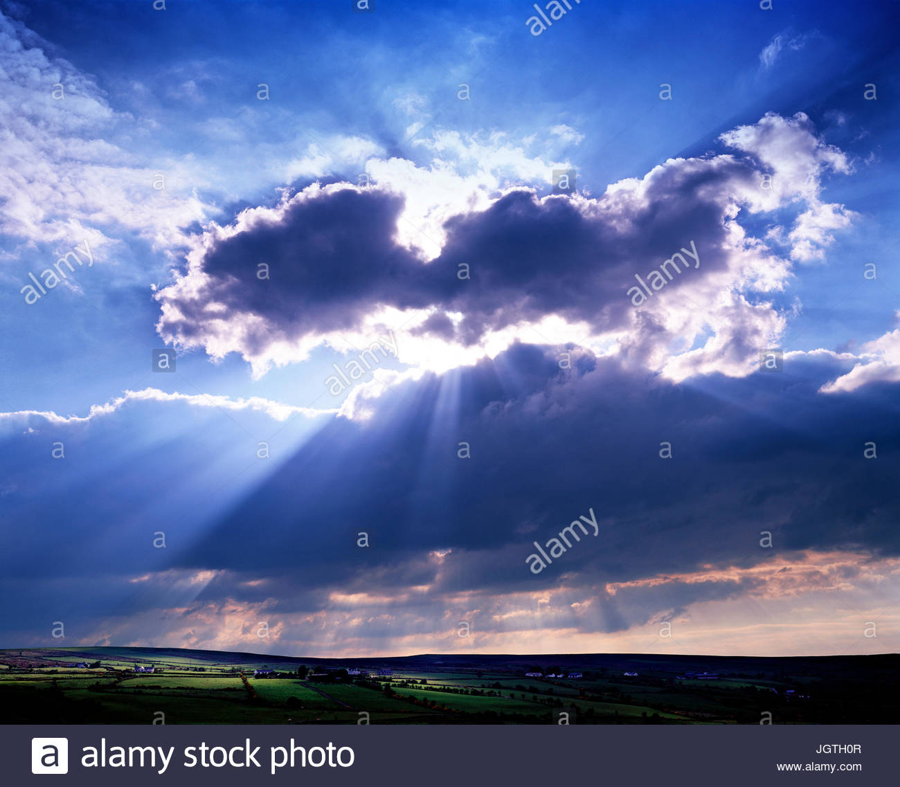 Sun shines out from behind clouds. - Stock Image
