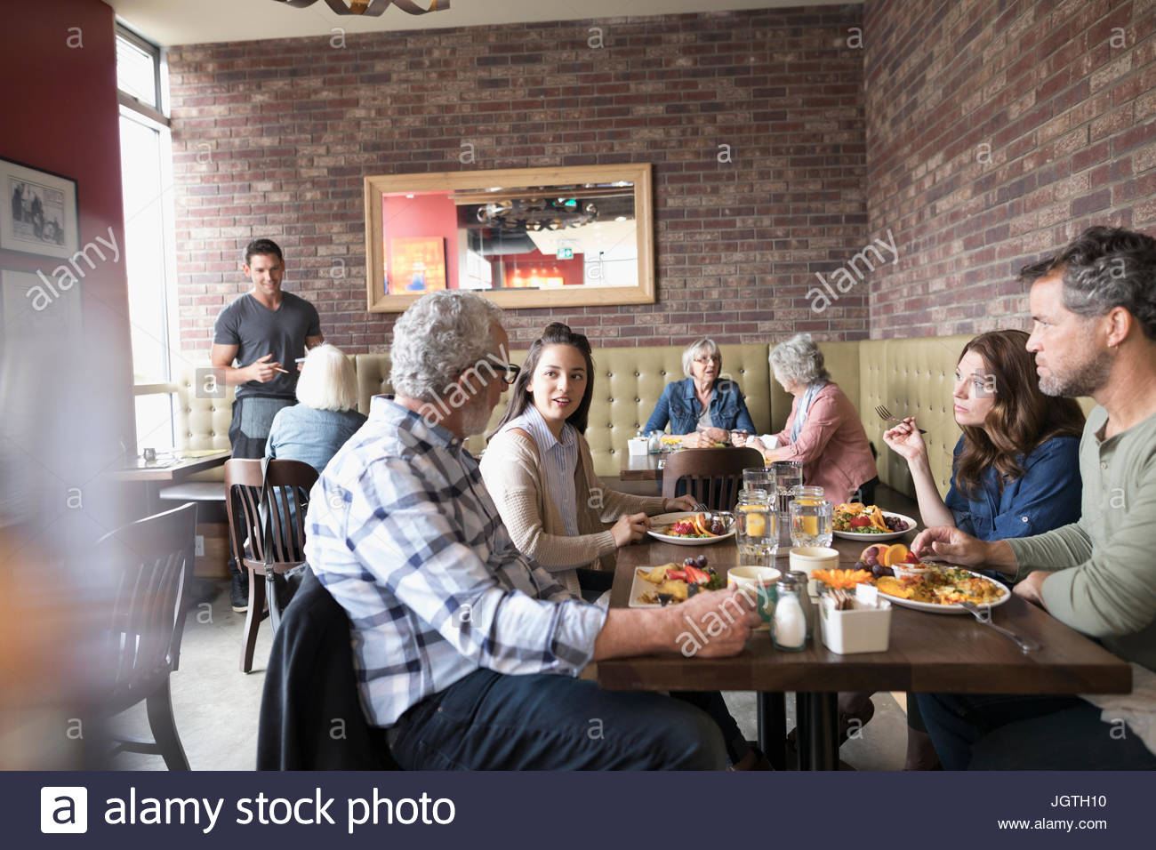 Multi-generation family eating brunch at diner table - Stock Image