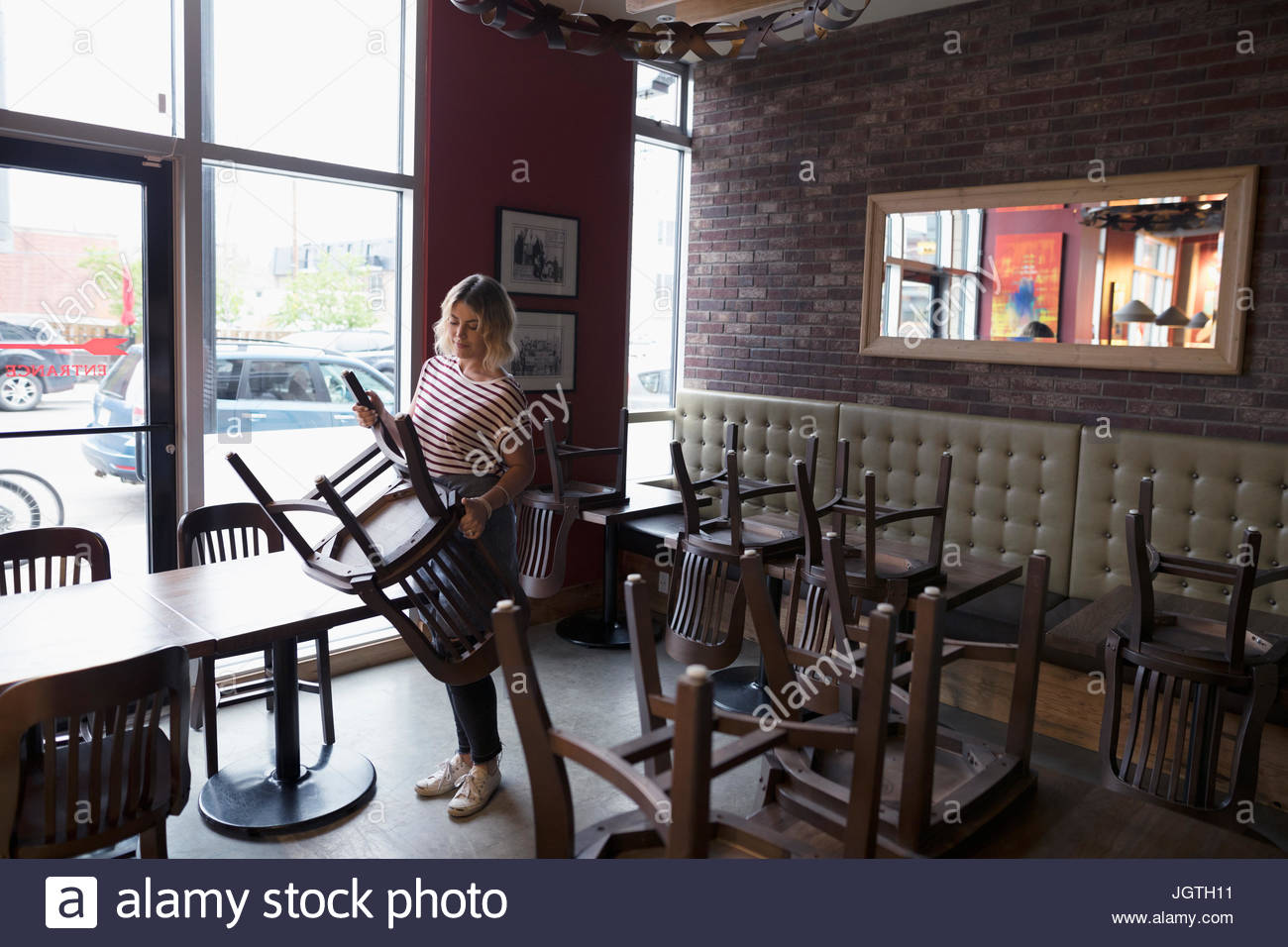 Waitress turning chairs onto tables, closing at diner - Stock Image