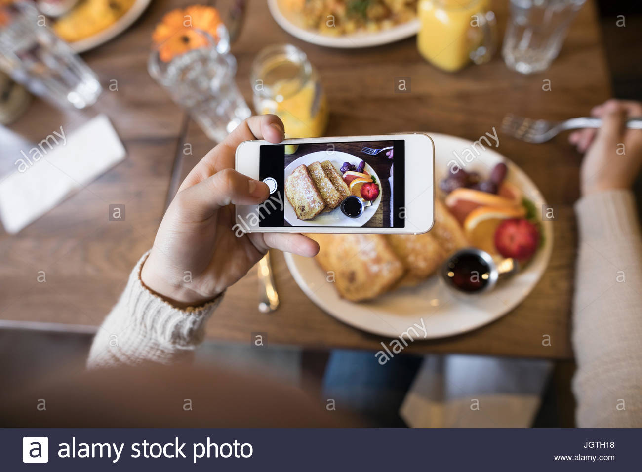 Personal perspective teenage girl photographing brunch food with camera phone - Stock Image