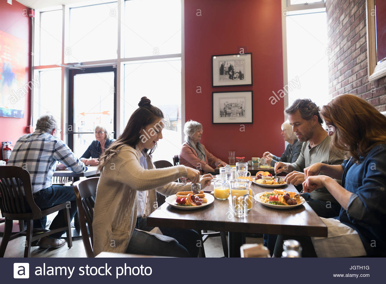 Parents with teenage daughter eating brunch at diner table - Stock Image