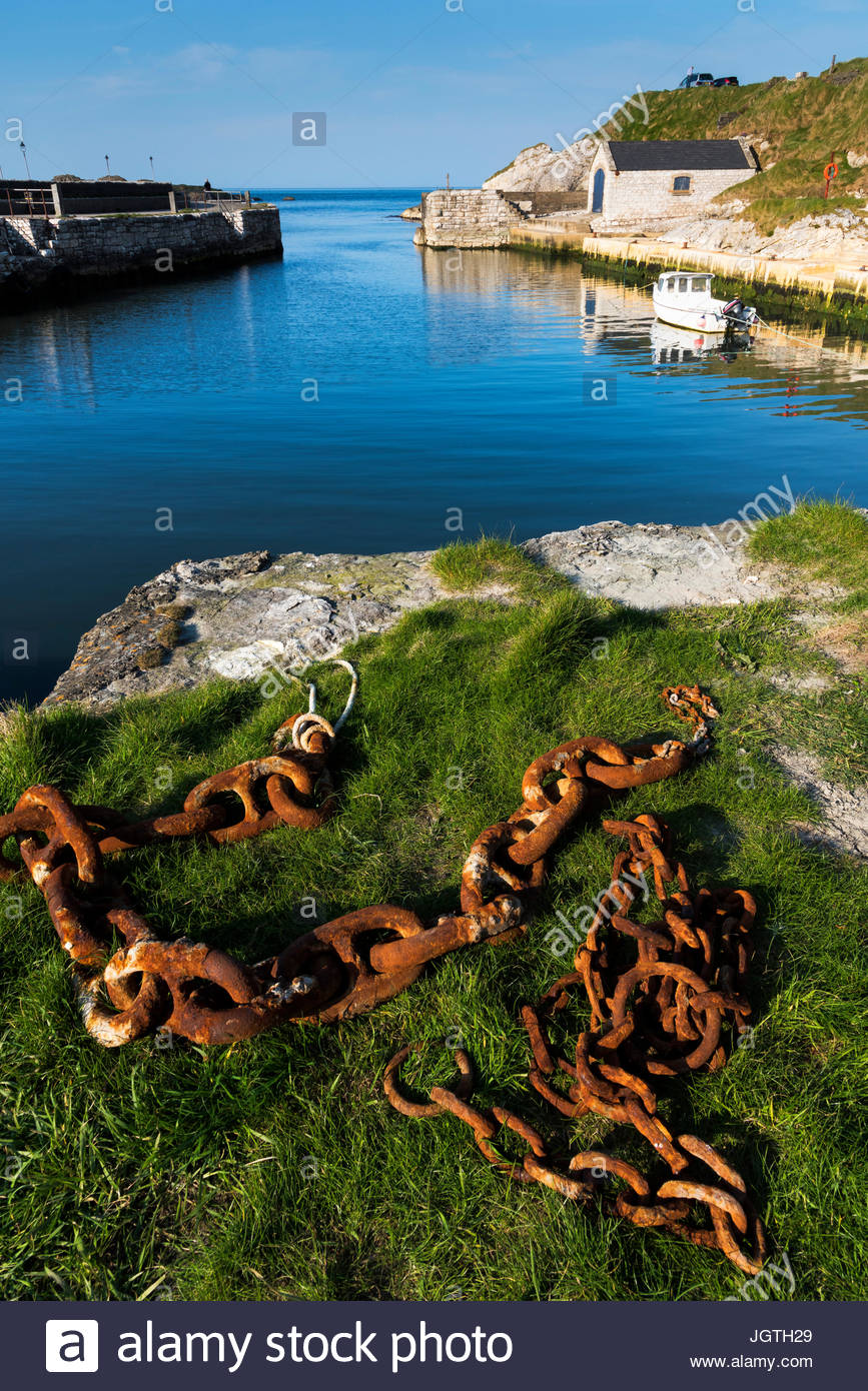 Rusted chains sit on the edge of a rock outcropping by Ballintoy Harbor. - Stock Image