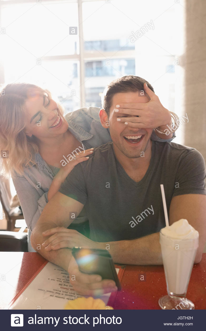 Playful girlfriend covering boyfriend - Stock Image