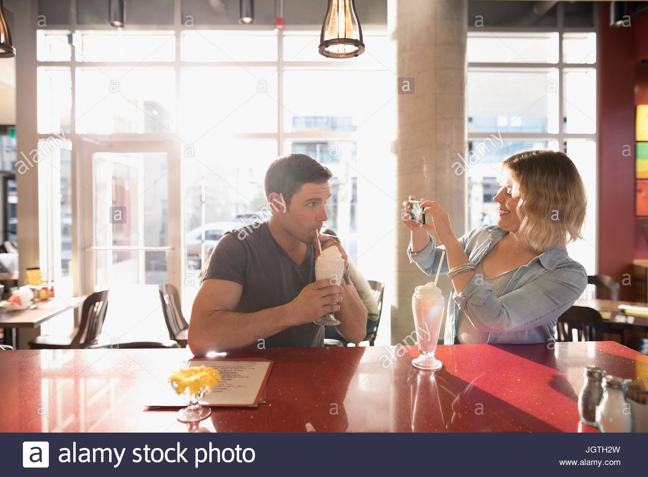 Girlfriend with camera phone photographing boyfriend drinking milkshake at diner counter - Stock Image