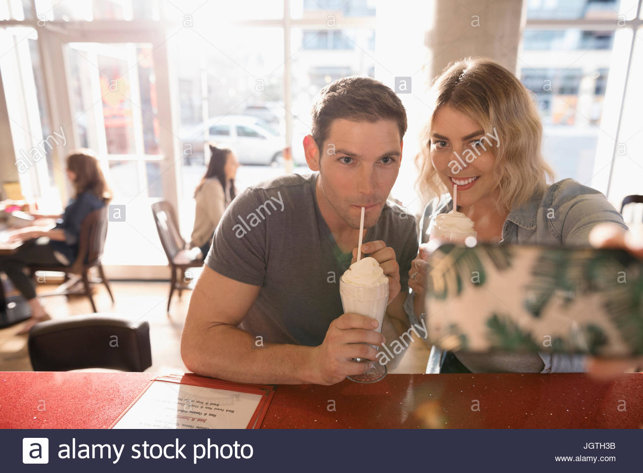Young couple drinking milkshakes, taking selfie with camera phone Stock Photo
