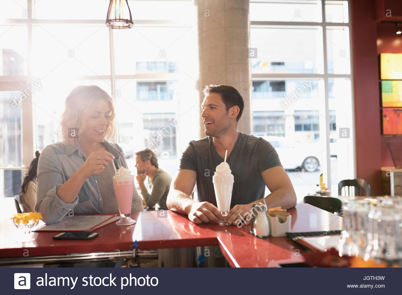 Young couple drinking milkshakes at diner counter - Stock Image