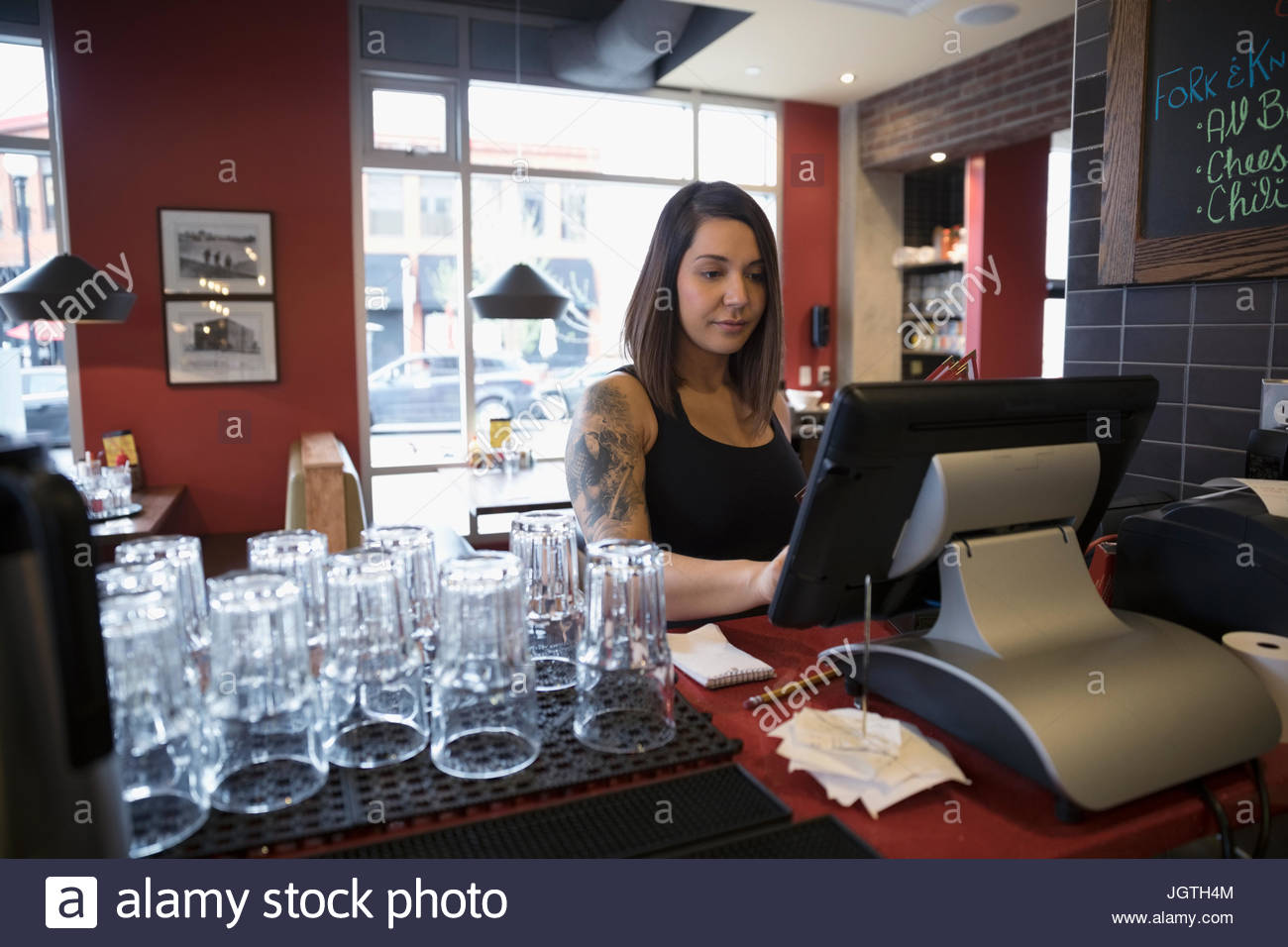 Tattooed waitress using computer, inputting order in restaurant - Stock Image