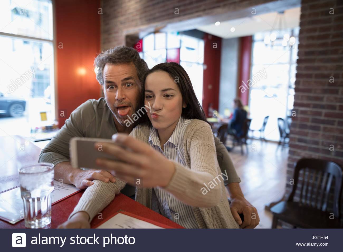 Father and teenage daughter taking selfie at diner counter - Stock Image