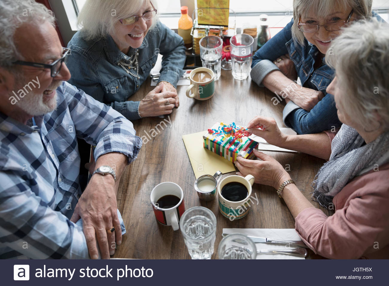 Senior friends celebrating birthday, opening gift in diner - Stock Image