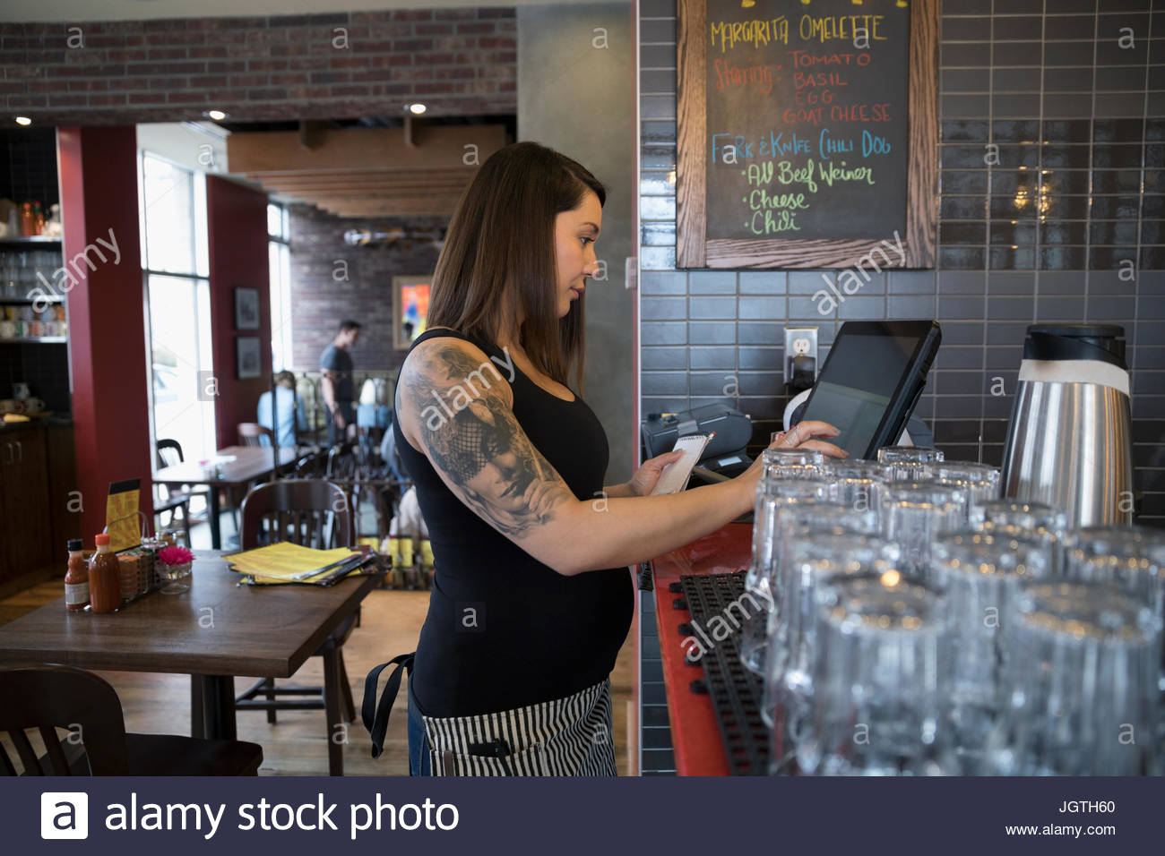 Pregnant tattooed waitress using computer, inputting order in restaurant - Stock Image