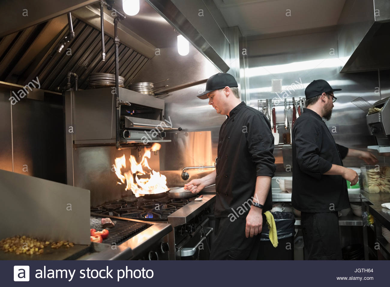 Line cooks preparing food, sauteing at stove in restaurant kitchen - Stock Image