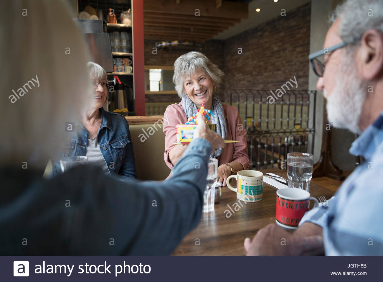 Smiling senior woman receiving birthday gift from friend in diner booth - Stock Image
