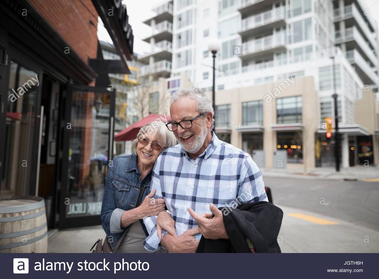 Smiling, affectionate senior couple walking on urban sidewalk - Stock Image