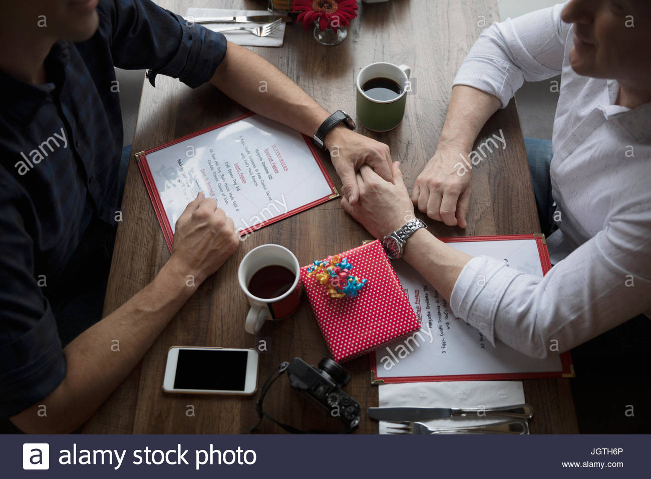Affectionate male gay couple holding hands, celebrating birthday at diner booth - Stock Image