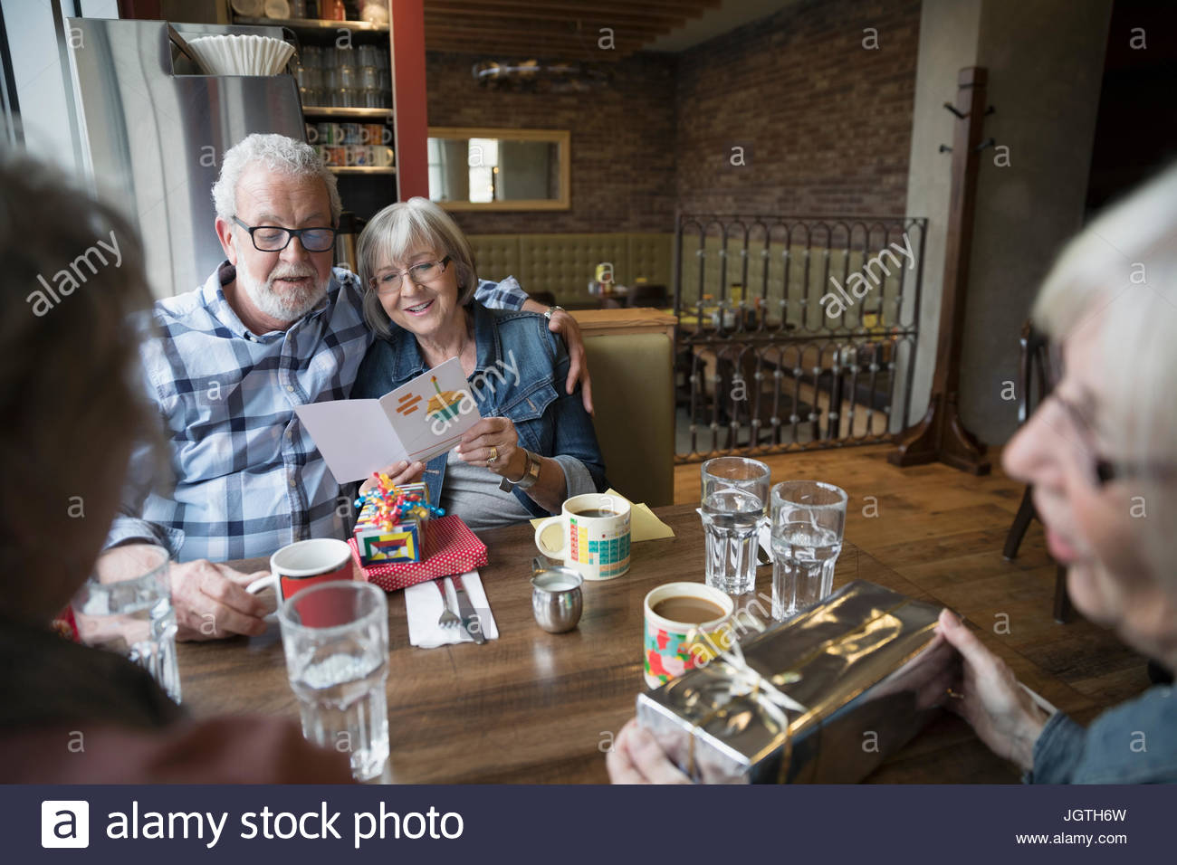 Senior friends celebrating birthday, reading greeting card in diner booth - Stock Image