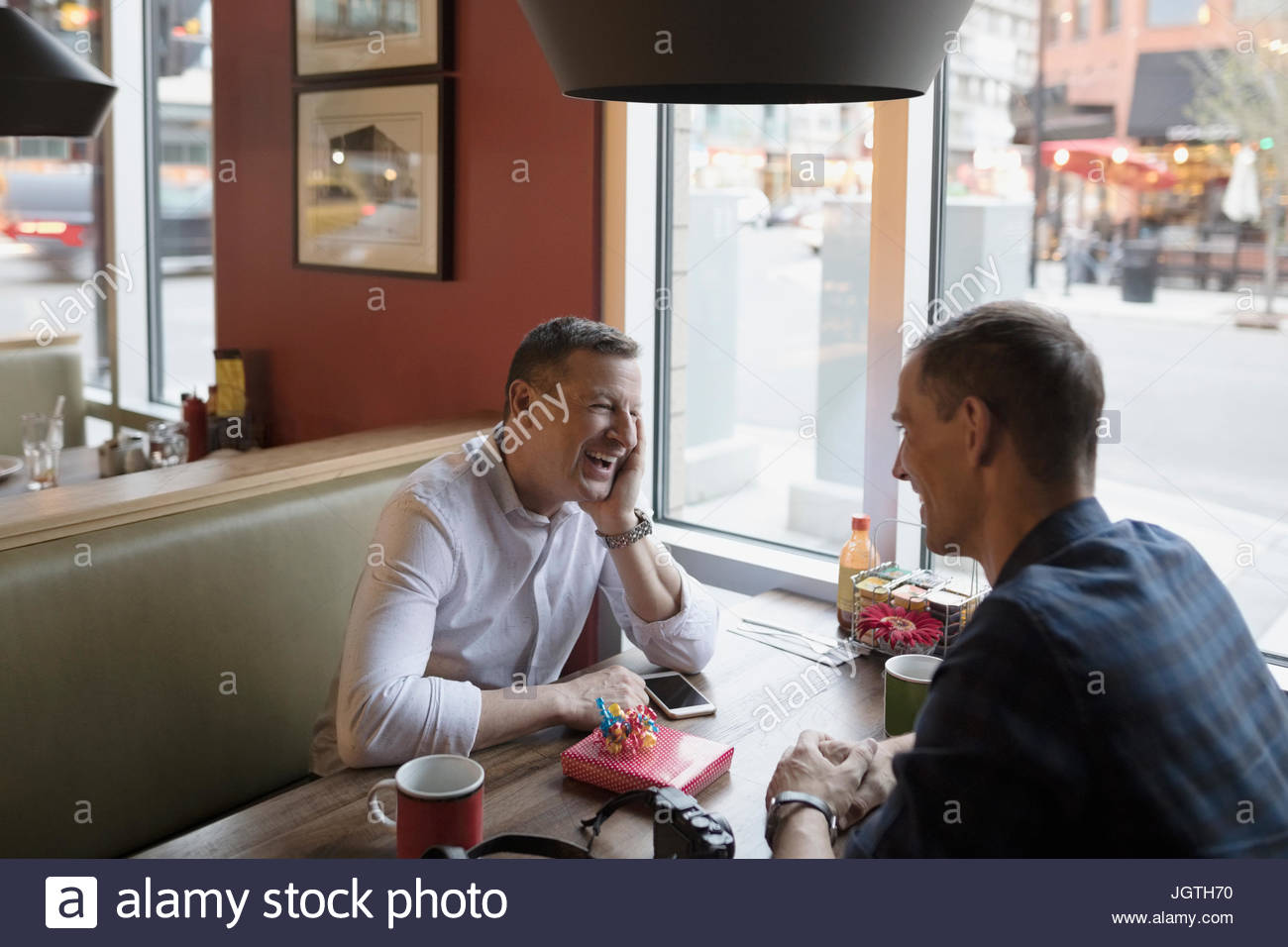 Smiling male gay couple celebrating birthday at diner booth - Stock Image