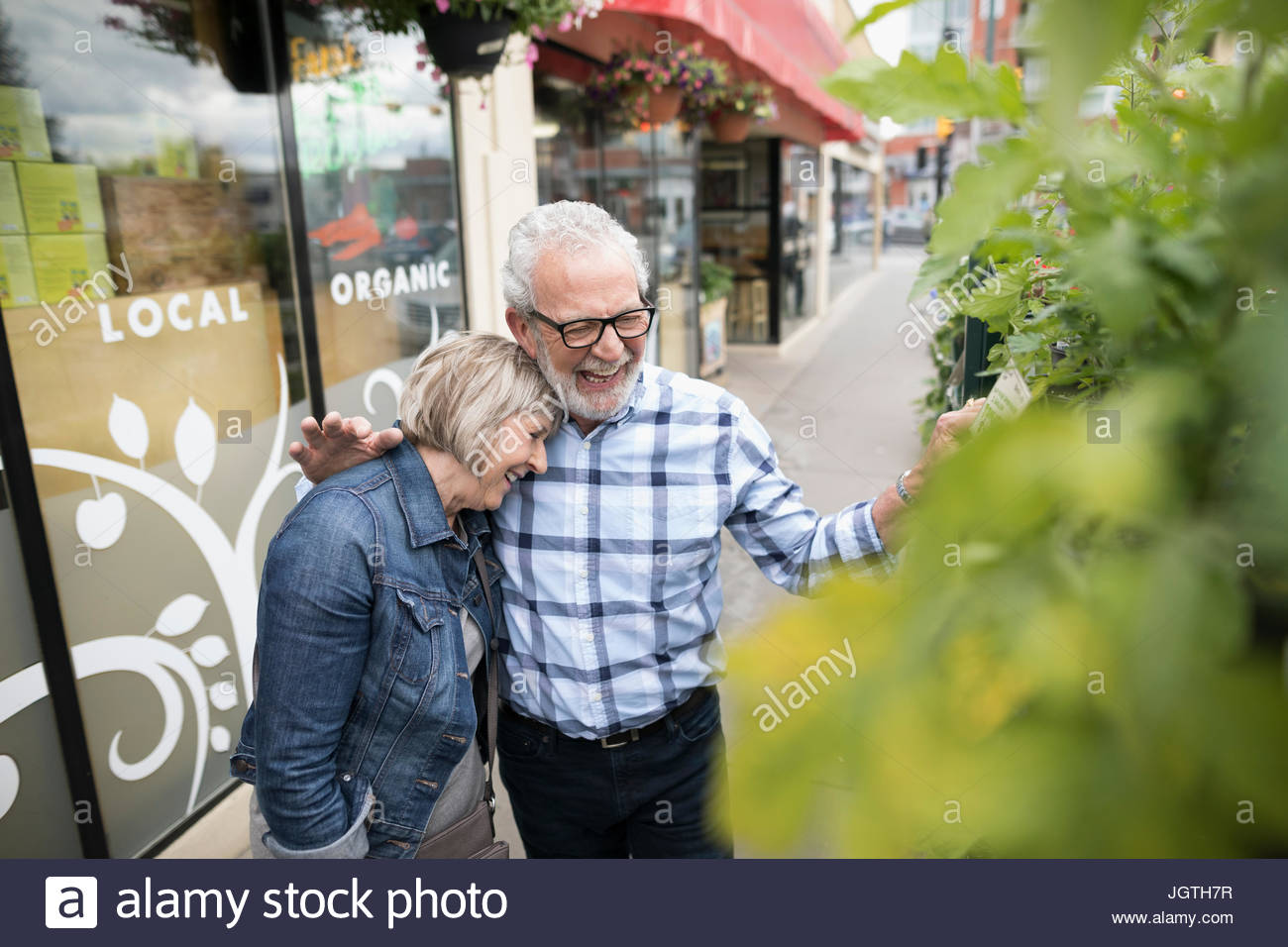 Laughing, affectionate senior couple shopping for plants at urban storefront sidewalk - Stock Image