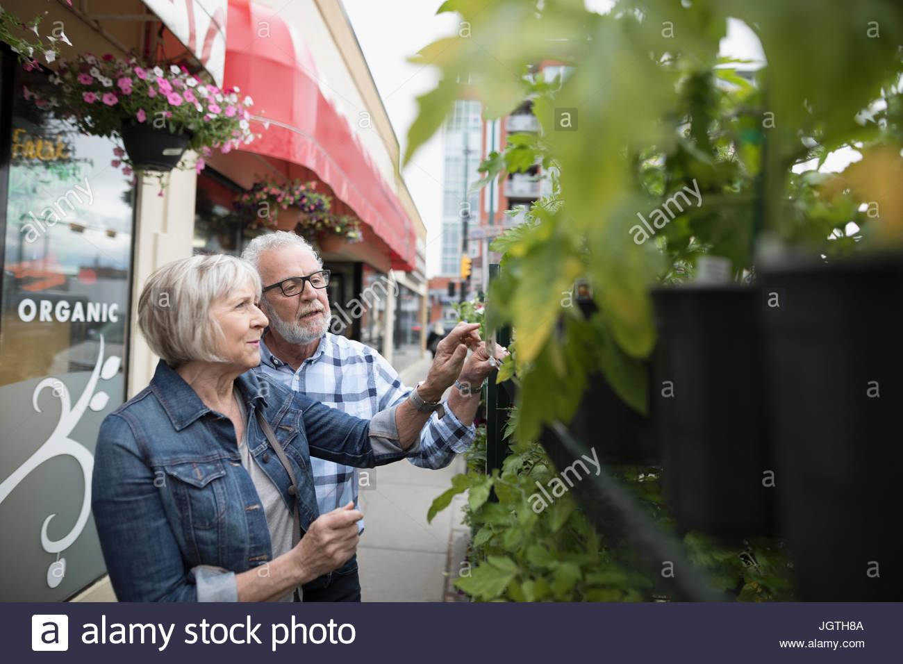 Senior couple shopping for plants at urban storefront sidewalk - Stock Image