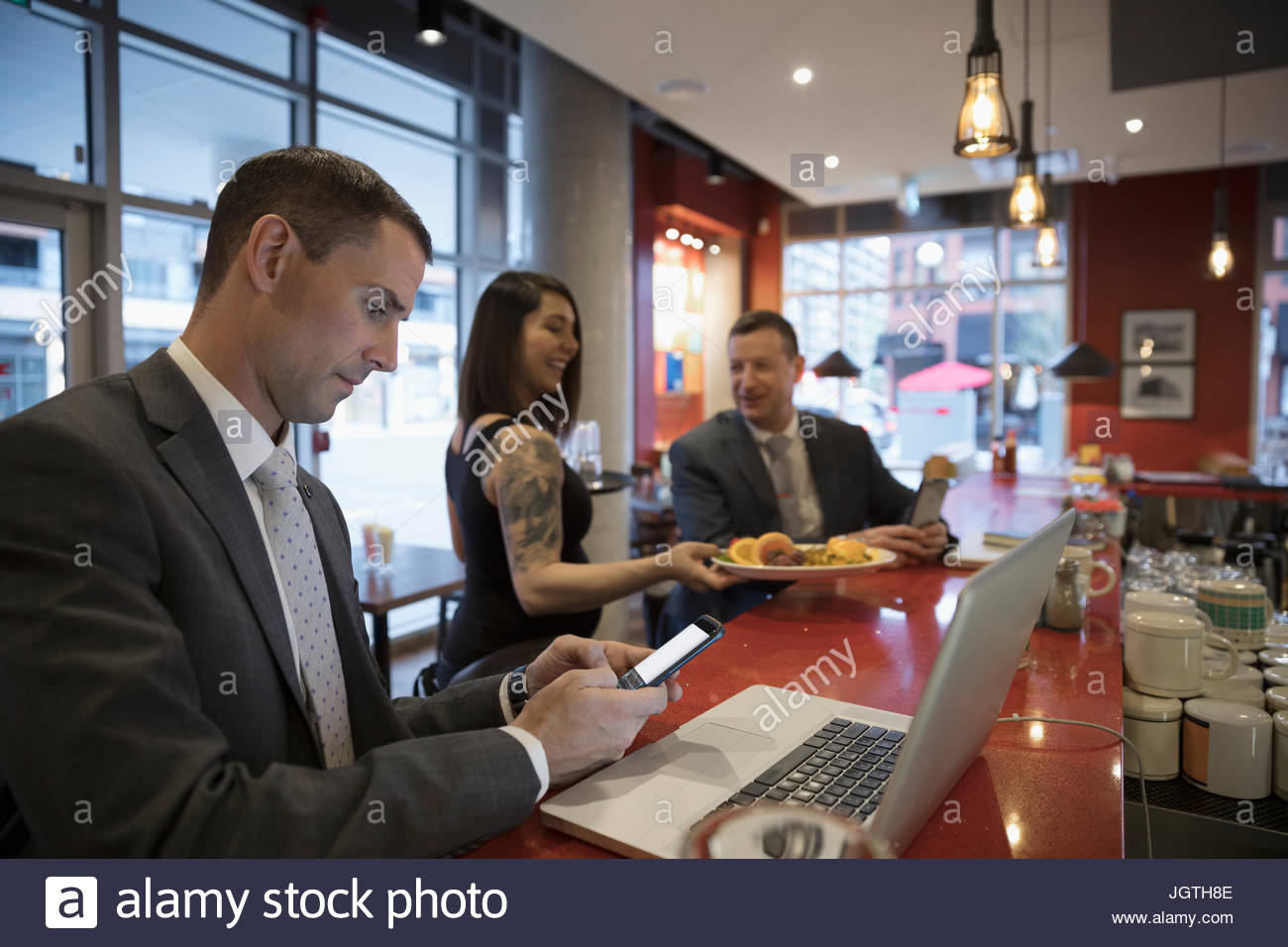 Waitress serving food to businessman working at diner counter - Stock Image