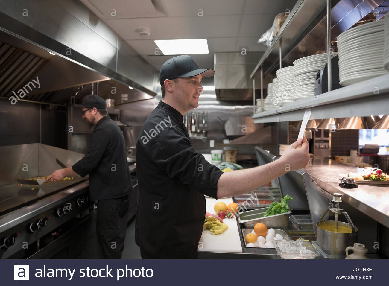 Line cooks preparing food in restaurant kitchen - Stock Image