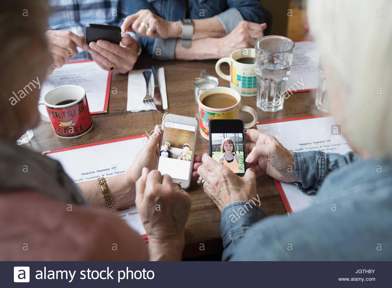Senior women friends sharing digital photographs of grandchildren on camera phones in diner - Stock Image