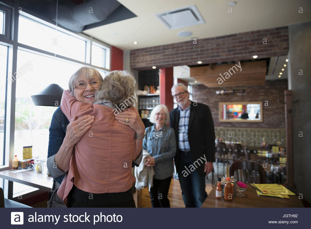 Senior friends greeting, hugging in diner - Stock Image