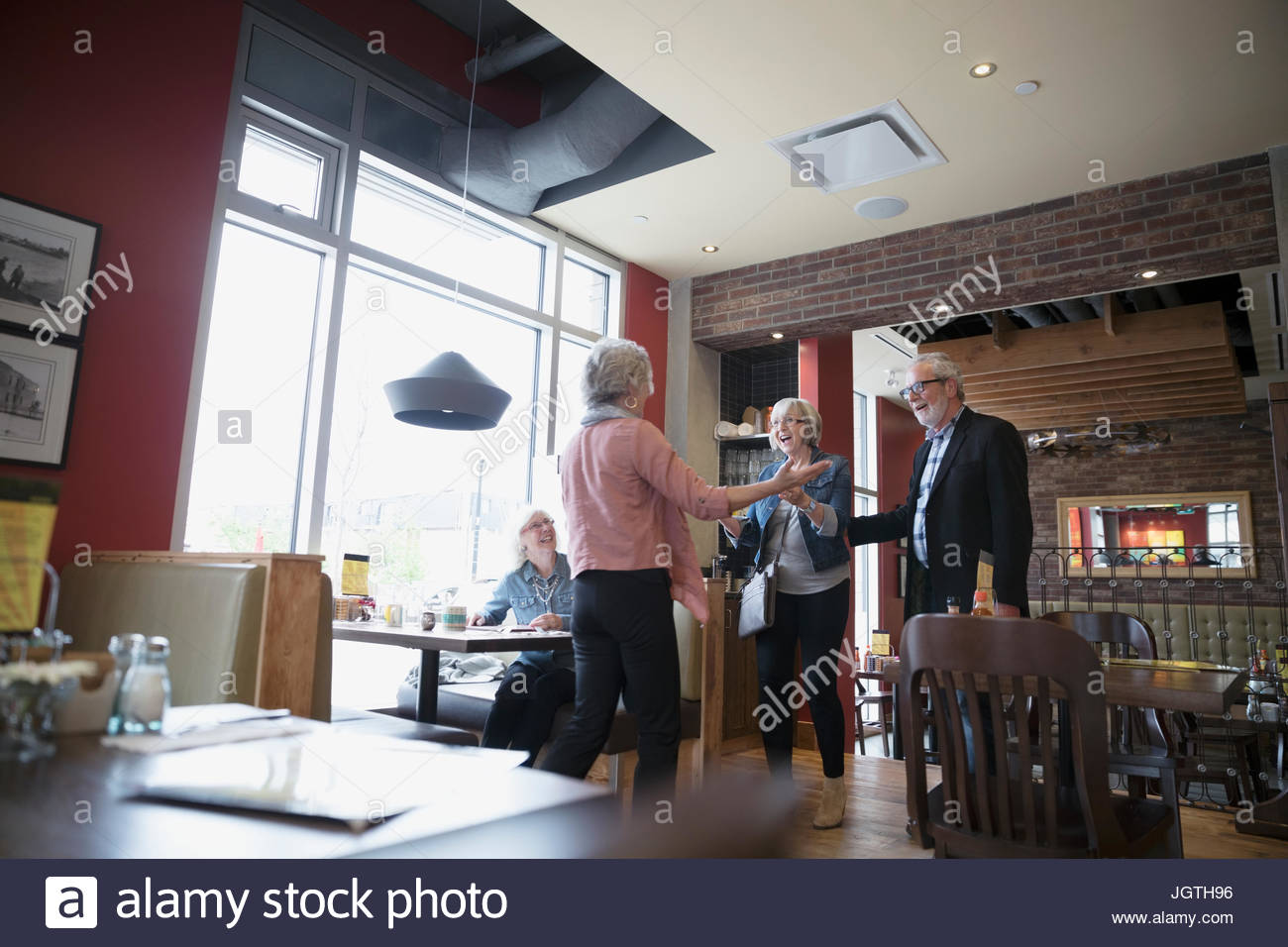 Enthusiastic senior woman greeting friends at diner booth - Stock Image