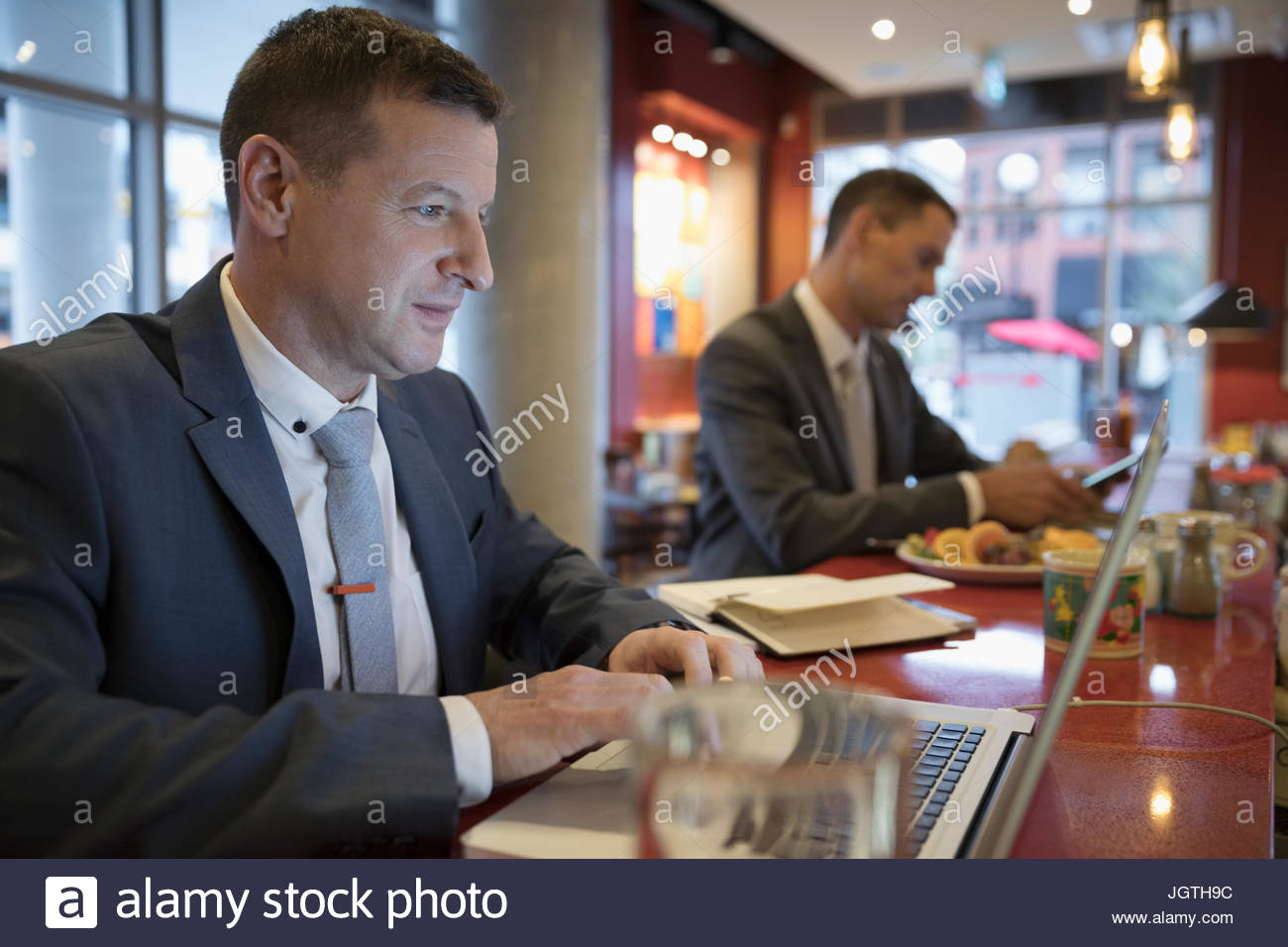 Businessman using laptop at diner counter - Stock Image
